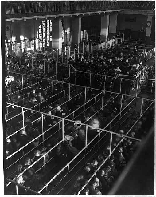 "[Emigrants in ""pens"" at Ellis Island, New York, probably on or near Christmas --note the decorations]"