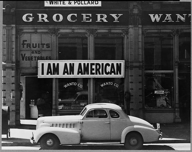 "Oakland, Calif., Mar. 1942. A large sign reading ""I am an American"" placed in the window of a store, at 13th and Franklin streets, on December 8, the day after Pearl Harbor. The store was closed following orders to persons of Japanese descent to evacuate from certain West Coast areas. The owner, a University of California graduate, will be housed with hundreds of evacuees in War Relocation Authority centers for the duration of the war"