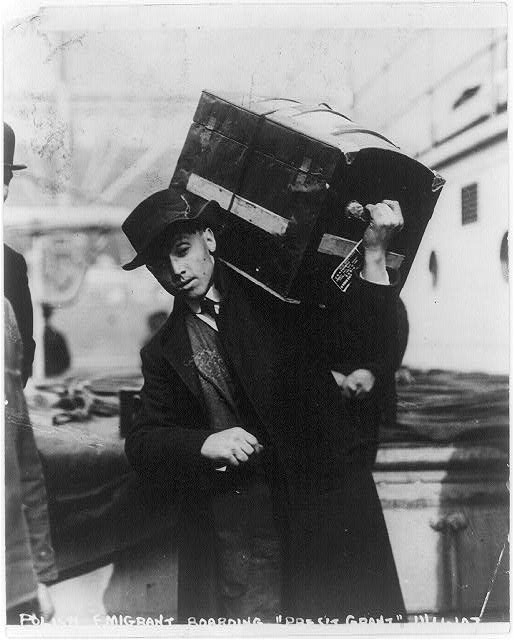 A Polish emigrant boarding ship - he carries trunk on his shoulders