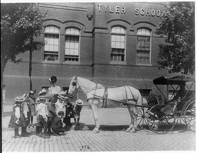 [Children studying a horse and buggy outside the Tyler School, Washington, D.C.]