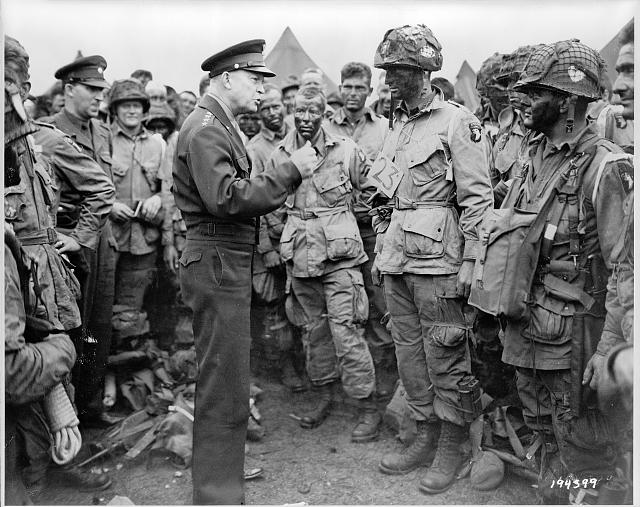 "General Dwight D. Eisenhower gives the order of the day, ""Full victory--nothing else"" to paratroopers somewhere in England, just before they board their airplanes to participate in the first assault in the invasion of the continent of Europe"