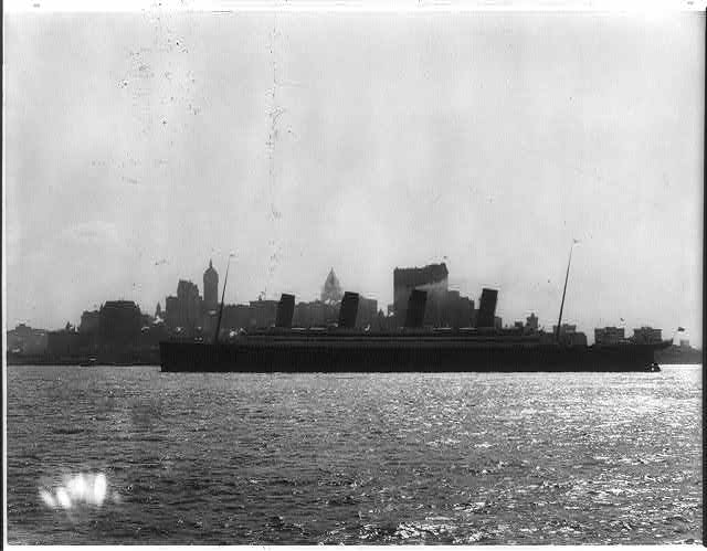 [The S.S. OLYMPIC, 1911: Full lgth. port view with New York skyline in backgrd.]