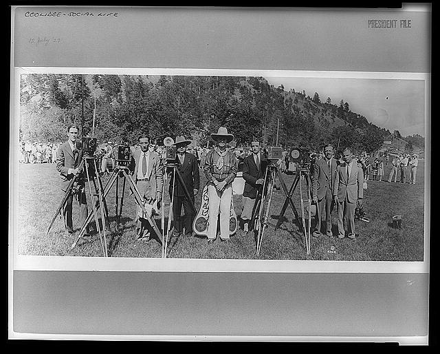 [President Coolidge in cowboy outfit, standing in field with photographers; mountain in background]