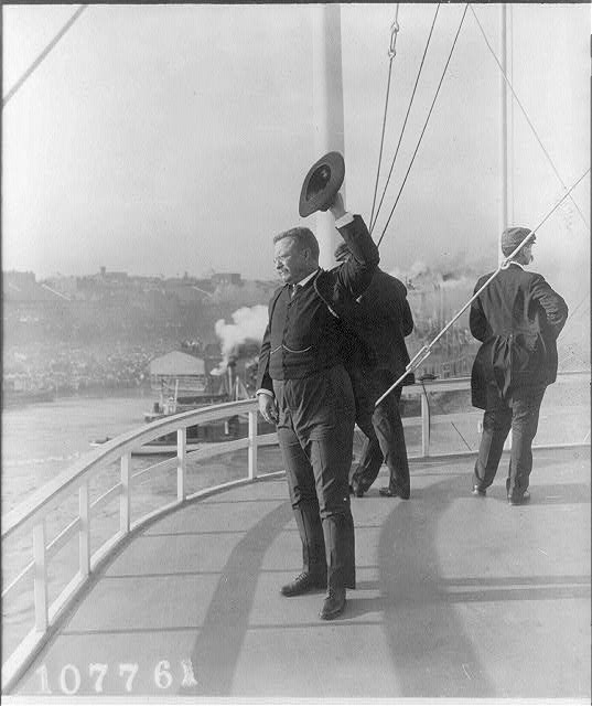 [Theodore Roosevelt standing on deck of ship and waving with his hat]