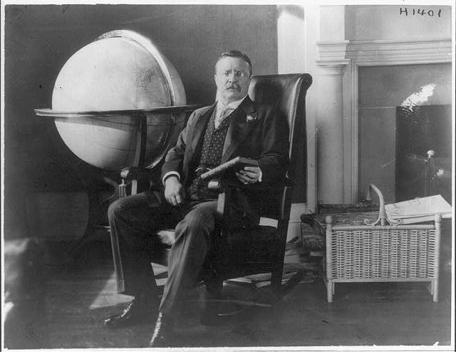 [Theodore Roosevelt, full-length portrait, seated next to a globe]