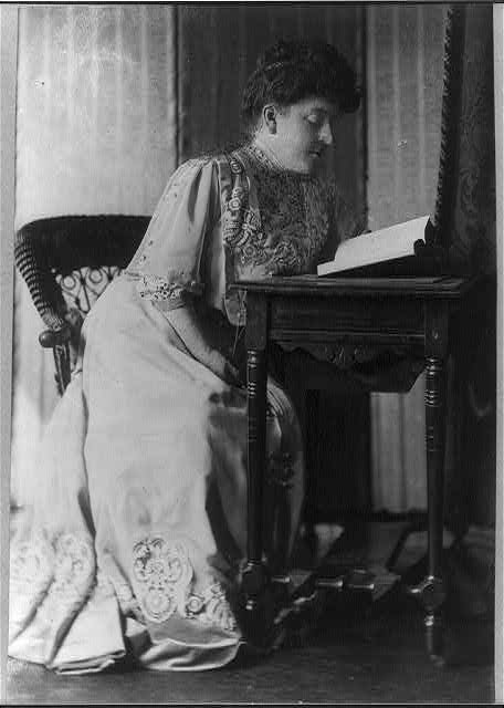 [Frances Hodgson Burnett, full-length portrait, seated, reading at a table]