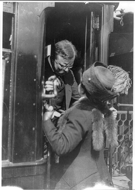 Antwerp, Belgium. T. Roosevelt talking with woman on car step