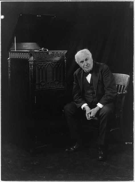 [Thomas Edison, seated beside phonograph]
