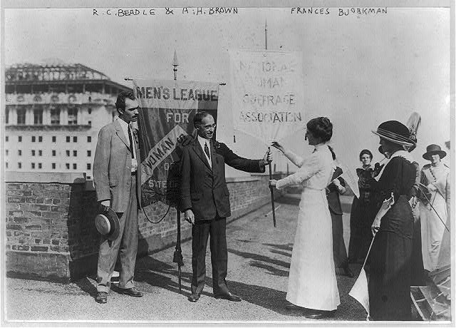 [R.C. Beadle and A.H. Brown of Men's League for Woman Suffrage of N.Y. receiving National Woman Suffrage Assoc. banner from Frances Bjorkman in rooftop ceremony. NYC. ca. 1915]