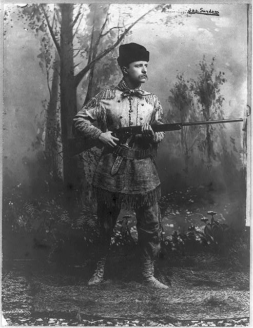 [Theodore Roosevelt, full-length portrait, standing, facing right, in deer skin hunting suit, holding rifle]