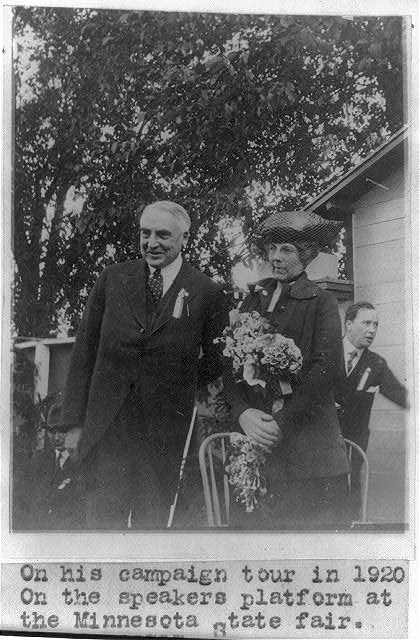 [Warren Gamaliel Harding; three-quarters length, standing with wife on platform at Minnesota State Fair, 1920 campaign]