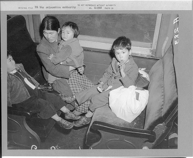 [Mother and three children on train from Los Angeles to Manzanar]