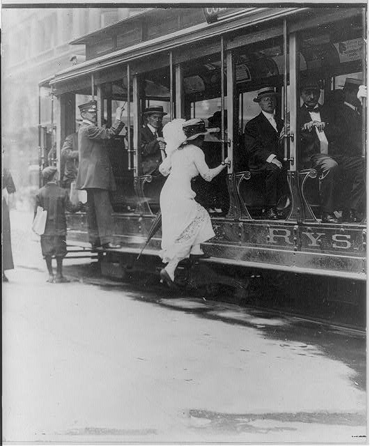 [Woman boarding NYC streetcar by jumping onto running board. 1913]