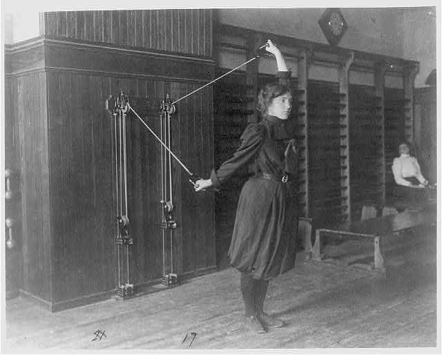 Female student exercising with a wall-mounted device using ropes and pulleys, Western High School, Washington, D.C.