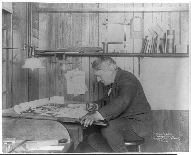 [Thomas Alva Edison, 1847-1931, left profile, seated at his desk, writing]
