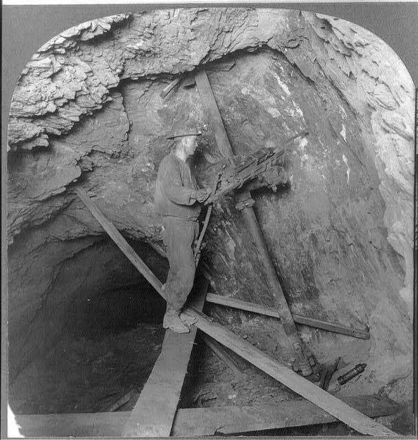Miner drilling copper rock with Leyner machine. Preparatory for blasting; Calumet-Hecla Mines, Calumet, Michigan