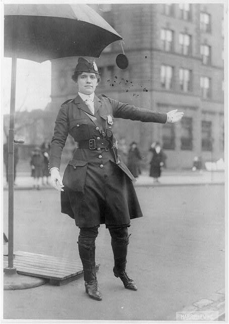 [Mrs. L.A. King, full, standing, directing traffic as policewoman]