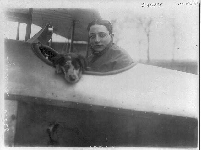[Victor Garaix, French aviator in cockpit of plane with dog]