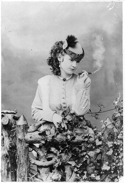 [Lotta Crabtree, half-length portrait, facing right, holding cigar]