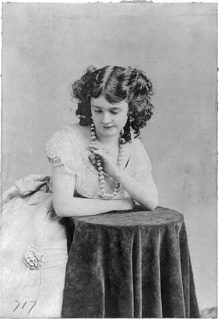 [Lotta Crabtree, half-length portrait, facing left, leaning on table, looking down]