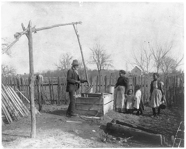 Negro man, woman and three children at an old-time well