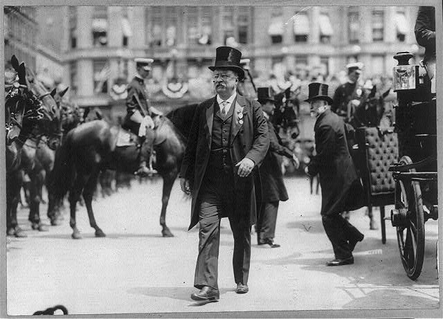 [Theodore Roosevelt walking in top hat, tails, and medal; with men, carriage, and horses in background]
