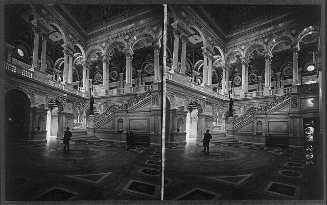 [The Great Hall of the Library of Congress - man standing in center, looking up, and woman seated on bench]