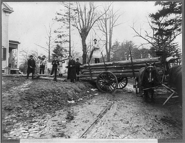 [Men loading logs on a horse-drawn wagon, from the original Abraham Lincoln log cabin, at College Point, N.Y., on Feb. 21, 1906, to be re-erected on the Lincoln Farm at Hodgenville, Kentucky, the birthplace of Lincoln]