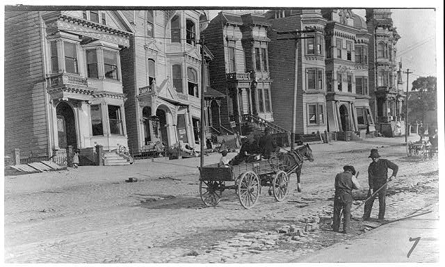 [Two men cleaning street, horse-drawn wagon and damaged buildings in the background, after the 1906 San Francisco earthquake]