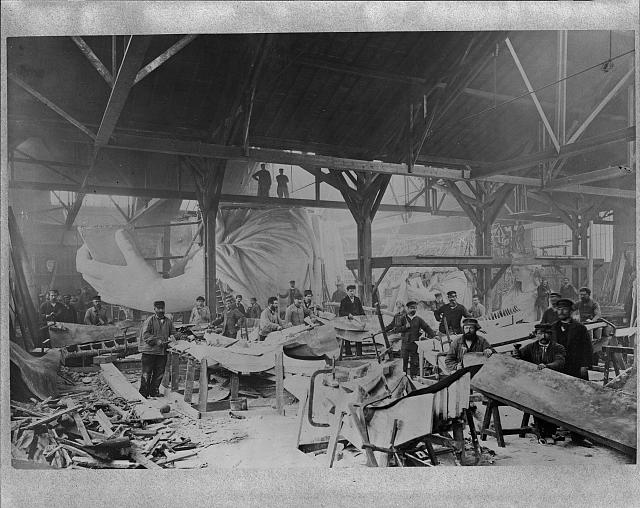 [Workmen constructing the Statue of Liberty in Bartholdi's Parisian warehouse workshop; first model; left hand; and quarter-size head-; Winter 1882?]