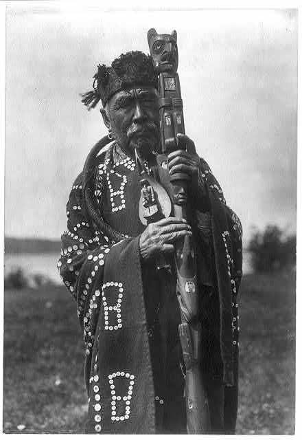 Hamasaka in Tluwulahu costume with speaker's staff--Qagyuhl [principal chief]