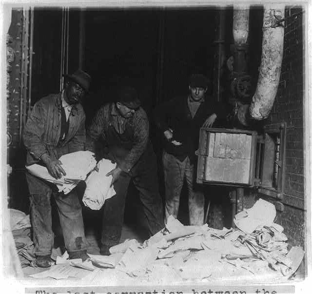 Three men throwing ballots, tally sheets and poll books of the Newberry election of 1918 into furnace at the U.S. Capitol Power House - they were ordered to be burned by Federal Judge Tuttle of Detroit