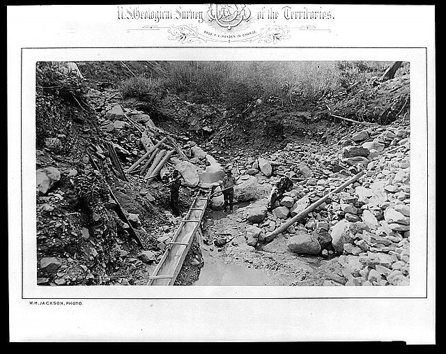 [Three men in gulch with a sluice, placer mining for gold]