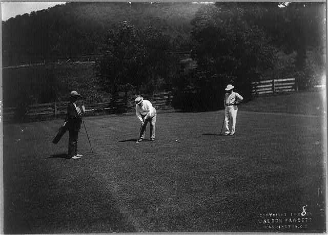 [William H. Taft, full length, facing left, bending over to hit golf ball, with 2 other men on green]