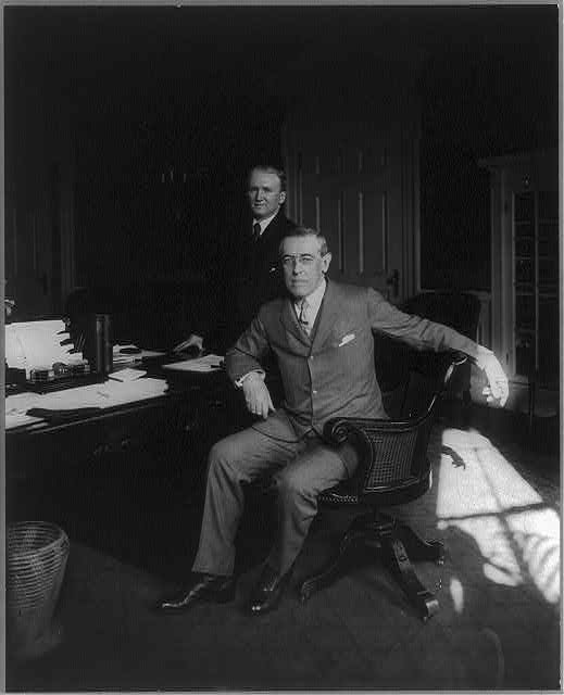 [Woodrow Wilson, full length, seated at desk, facing slightly left, with his private secretary Joseph Patrick Tumulty standing behind him]