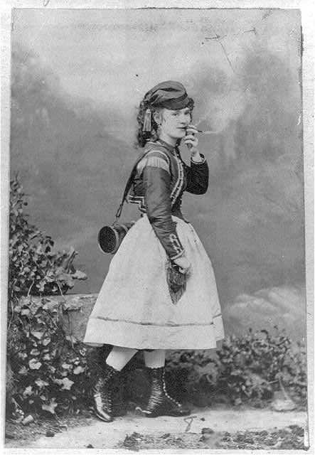 [Lotta Crabtree, full-length portrait in costume for a theatrical role, smoking a cigar]