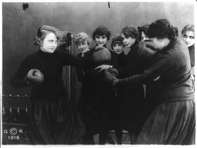 "[Stills of Billie Burke starring in motion picture, ""Gloria's Romance"", 1916: boxing with woman in gymnasium (198)]"