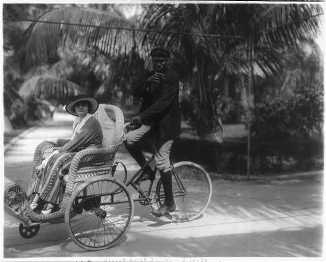 "[Stills of Billie Burke starring in motion picture, ""Gloria's Romance"", 1916: being driven in bicycle sedan chair (108)]"