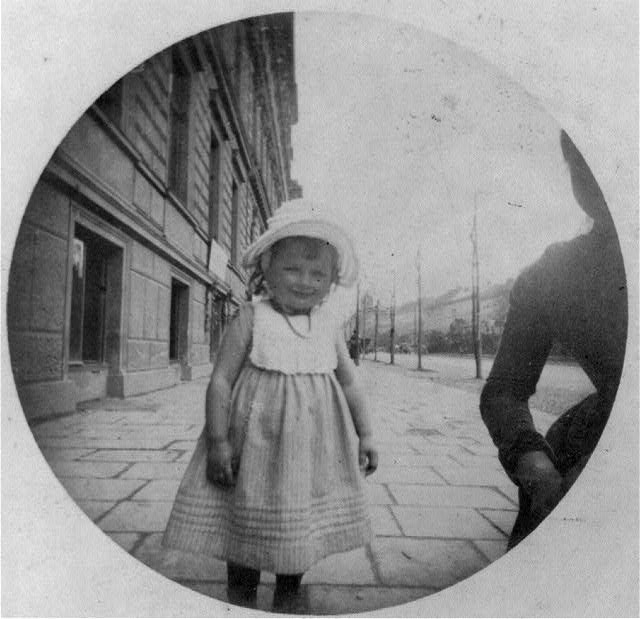 A small girl standing on sidewalk, three-quarters length, facing slightly right