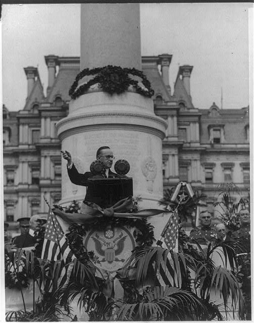 [Calvin Coolidge, head and shoulders, facing right, at base of the marble shaft erected to memory of the hero dead, in front of State, Navy and War Dept., dedicating memorial to heroes of First Division, American Expeditionary Forces]