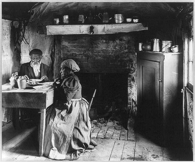 [Old African American couple eating at the table by fireplace, rural Virginia]