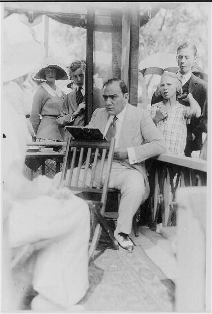 [Enrico Caruso, 1873-1921, drawing caricature sketches in booth at charity fair in Southampton, L.I., from right of sitter, onlookers in background]