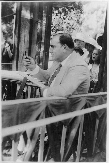 [Enrico Caruso, 1873-1921, drawing caricature sketches in booth at charity fair in Southampton, L.I., left profile with raised pencil]