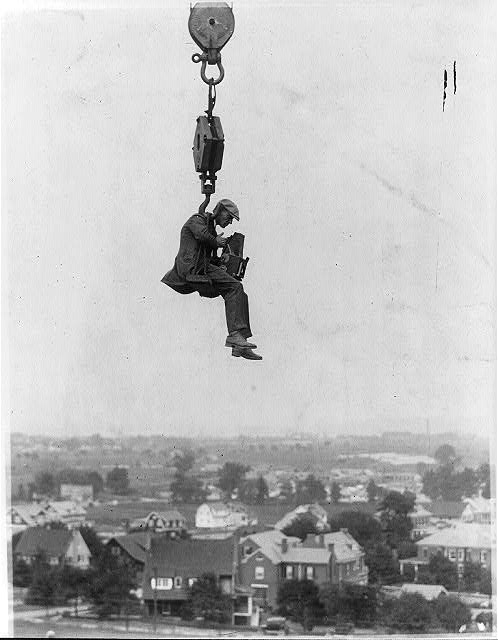 [Photographer with camera suspended from hook of a (crane?) high in the air]