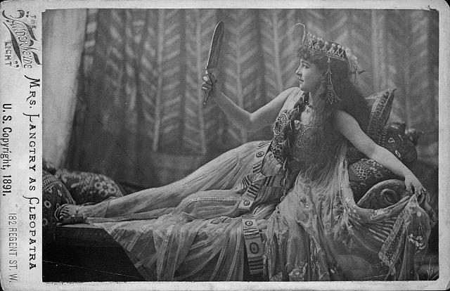[Lillie Langtry as Cleopatra, full-length portrait, lying on sofa and looking in mirror]