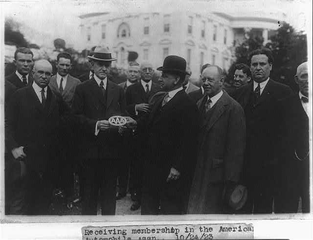 [Charles A. Frazer presents President Coolidge with an American Automobile Association emblem before a small gathering of AAA members on the White House lawn]