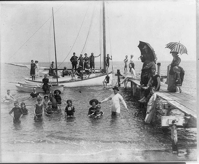 [Men, women, and children in bathing suits on dock, sailboats, and in water; Frances Benjamin Johnston sits on edge of small catboat]