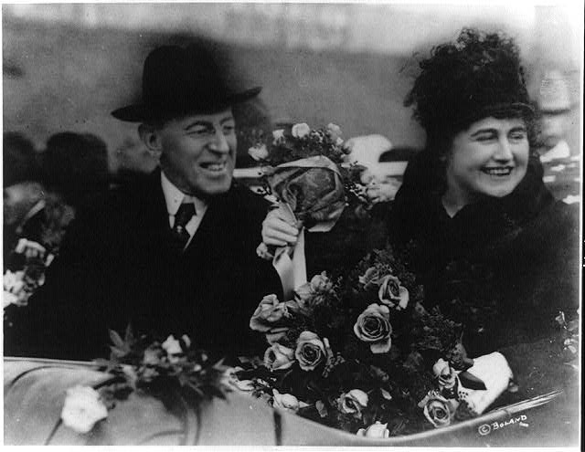 [Woodrow Wilson, half length, seated, facing right; and his wife (Edith Bolling Galt) holding flowers]