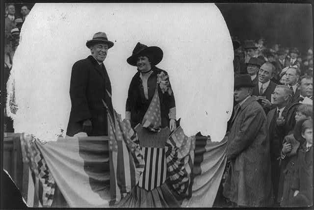 [Woodrow Wilson, half length, standing, facing right; and his wife (Edith Bolling Galt), on flag-draped platform in front of crowd]