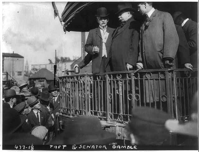 [William Howard Taft and Senator Gamble on back of train, in front of crowd]